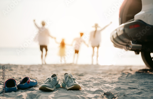 Obraz Close up on the shoes.Family vacation holiday, Happy asian family running on the beach in the sunset. Back view of a happy family on a tropical beach and a car on the side. - fototapety do salonu