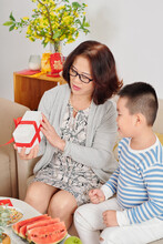Grandmother Giving Present For Lunar New Year To Her Grandson When They Are Sitting On Sofa In Living Room