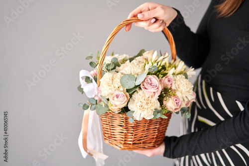 Small flower shop and Flowers delivery. Flower arrangement in Wicker basket. Beautiful bouquet of mixed flowers in woman hand. Handsome fresh bouquet. © malkovkosta