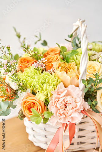 Small flower shop and Flowers delivery. Flower arrangement in Wicker basket. Beautiful bouquet of mixed flowers on wooden table. Handsome fresh bouquet. © malkovkosta