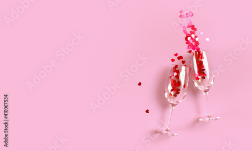 Valokuva Two clinking champagne glasses with splash of red heart shaped confetti over pink background