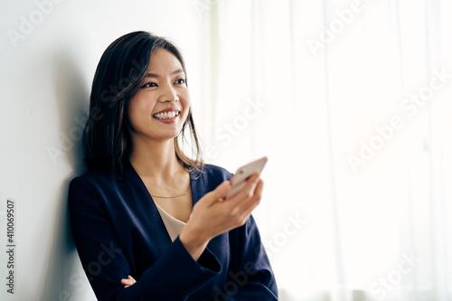 スマートフォンを持つ30代ビジネスウーマン