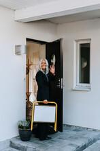 Female Estate Agent Standing In Open Entrance Door