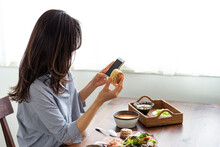 スマートフォンを見ながら食事をする女性