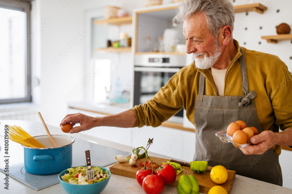 Fototapeta Happy retired senior man cooking in kitchen. Retirement, hobby people concept