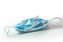 Paper Boats Sail On A Surgical Face Mask Like On The High Seas, Metaphor For Searching A Way Out Of The Coronavirus Crisis Or Dangerous Tourism During Covid-19 Pandemic, Copy Space