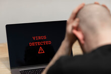 Virus Detected With A Warning Sign On A Laptop. A Desperate Man Sitting In Front Of His Computer With The Warning On His Screen. Cybercrime, Infected Unsafe Device