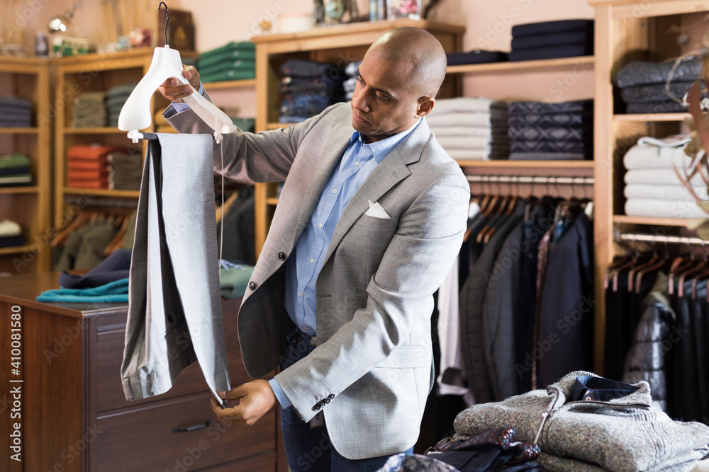 Fototapeta Portrait of young adult man choosing suit pants to new jacket in clothing store