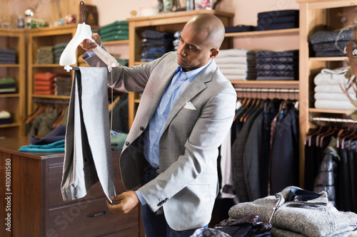 Obraz Portrait of young adult man choosing suit pants to new jacket in clothing store - fototapety do salonu