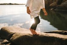Girl Walking On Rocks At Sea