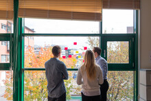 Coworkers Looking At Notes Sticked On Window