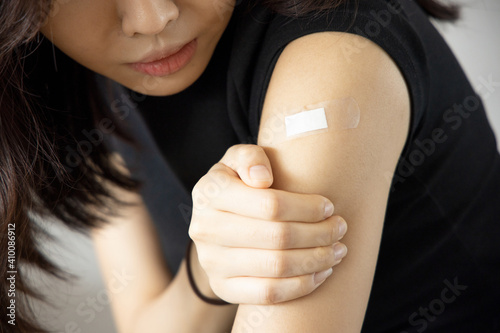 Obraz na plátně Asian woman receiving getting vaccinated immunity with bandage on her upper arm,