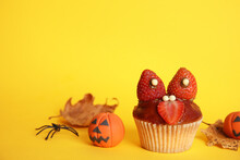 Delicious Cupcake Decorated As Monster On Yellow Background. Halloween Treat