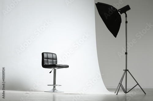 Fotomural Modern chair and professional lighting equipment in photo studio