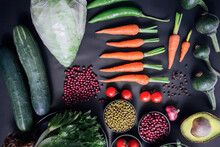 Top View Of Set Vegetables On A Black Background With Chili, Baby Carrots, Tomatoes, Beans, Green,red,red Onions, Lettuce,pepper, Pumpkin, Cinnamon, Cauliflower, And Avocados. Healthy Concept