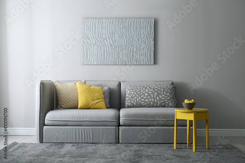 Obraz Stylish living room with sofa. Interior design in grey and yellow colors - fototapety do salonu