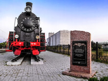 Buryn, Ukraine - August 18, 2018: An Old Steam Locomotive And A Memorial Plate To The Partisan Railroad Workers At The Putyvl Railway Station In Buryn (Sumy Region). Outdoor World War II Monuments