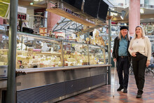 Senior Couple At Cheese Stand In Indoor Market