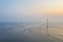 Wind Farm On Tidal Flat Wetland In Sunrise