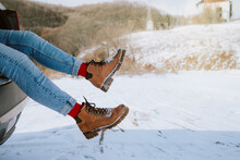 Female Legs In Winter Boots Happily Dangling Out A Car Trunk On Mountain Top Covered In Snow