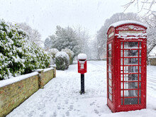 Snow Covered Village Post Box And Phone Box In Snowfall