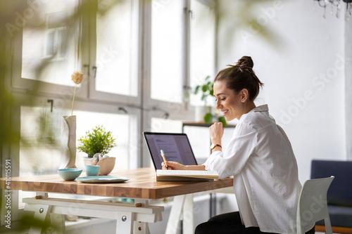 Creative young woman working on laptop in her studio Fototapeta
