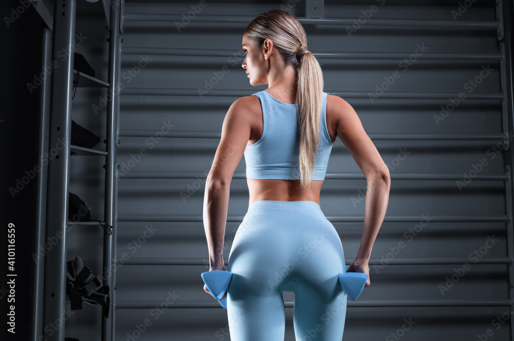 Fototapeta Beautiful tall blonde posing in the gym with dumbbells in her hands against the background of the wall bar. The concept of sports, fitness, aerobics, bodybuilding, stretching. Back view.