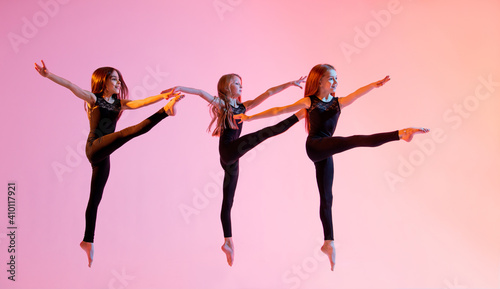 Obraz na plátně group of three ballet girls in black tight-fitting suits jumping on red background with their long hair down