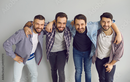 Leinwand Poster Portrait of happy friends standing with arms around each other's shoulders in studio with light gray background