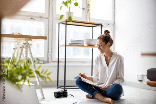 Obraz Young female freelancer working in loft office  - fototapety do salonu
