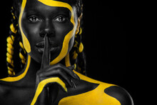 Face Art. Girl Showing Gesture Quietly, Asks Remain Silent With Finger. Woman With Black And Yellow Body Paint. Young African Girl With Colorful Bodypaint. An Amazing Afro American Model With Makeup.