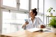 Leinwandbild Motiv Creative business woman using smartphone in loft office