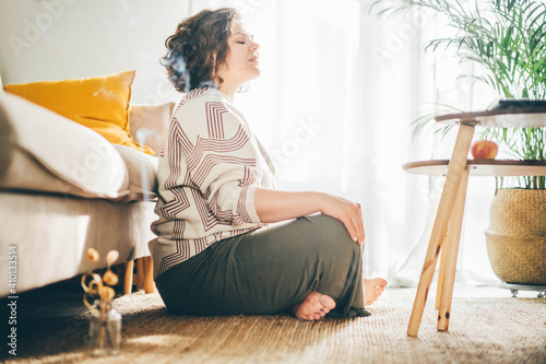 Fotografia Plus size woman doing yoga and meditation at home.