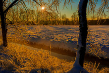 Sunrise Over An Agricultural Area With Snow In Germany , In The Foreground A Small River And Trees