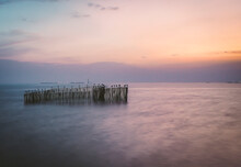 Long Exposure Wooden Pole In Sea At Dusk. Pastel Blue And Pink Sky In Bangpu Thailand