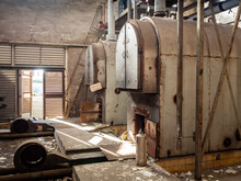 Old Cast Iron And Steel Industrial Vintage Oil And Coal Heating Boilers In Abandoned Dark And Gloomy Boiler Room With Pipes And Fans Decaying And In Need Of Maintenance