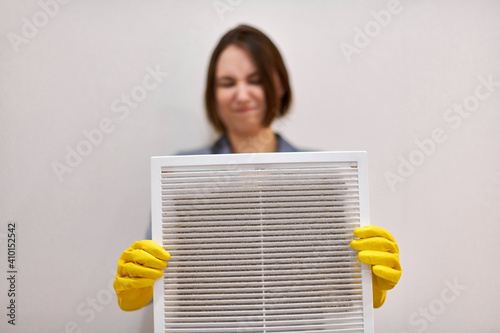 Fotomural Woman holding dirty and dusty ventilation grille, disgusted