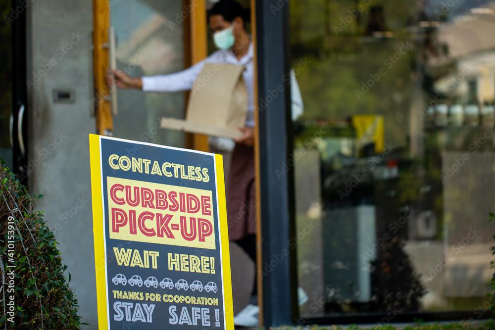 Fototapeta Curbside pick up.Store worker wear mark and bring  foods