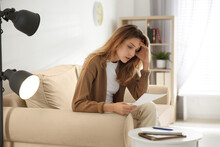 Worried Woman Reading Letter On Sofa At Home
