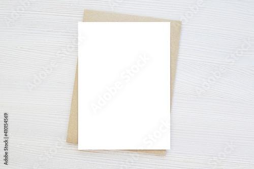 Blank vertical card mockup, invitation, greeting card mock up, brown envelope, wooden background, minimal style.