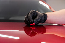 The Master Removes Small Dirt Pieces From The Car Bonnet Surface With Special Clay Before Polishing. Professional Car Washing And Detailing Process.