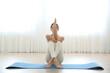 Young woman practicing eagle asana in yoga studio. Garudasana pose
