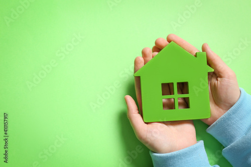 Woman holding house model on light green background, top view. Space for text © New Africa