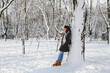 canvas print picture - Young smiling woman standing near to a big tree in a snow-covered winter park. Snowy winter