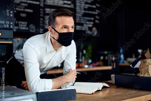 Obraz Portrait of worried cafe small business owner wearing mask behind the counter - fototapety do salonu
