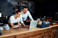 Happy Small Business Owners Working With Laptop At Cafe
