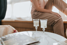 Photo Of Two Crystal Glasses With Champagne And Magazine On Marble Table Against Background Of Sitting Woman