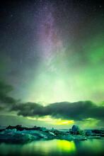 Aurora Boreal Y Via Lactea Con Algunas Nubes Sobre Un Lago Con Icebergs En Jökulsárlón, Islandia