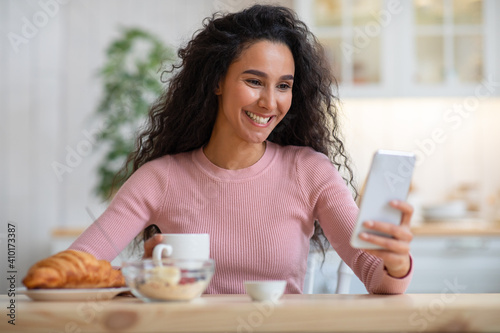 Smiling black woman using smartphone while having breakfast in kitchen at home © Prostock-studio