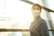 Leinwandbild Motiv attractive asian female woman casual cloth wearing face mask protection standing next to big glasses modern frame window with sun light flare subset moment new normal lifestyle healthcare concept